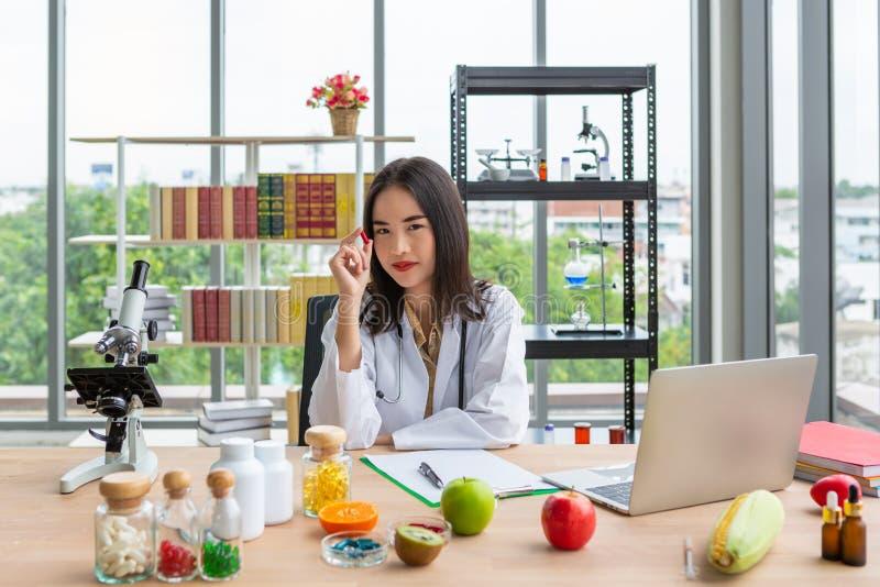 Donna asiatica di medico del dietista che mostra la perla molle rossa degli integratori alimentari in mano destra fotografia stock libera da diritti
