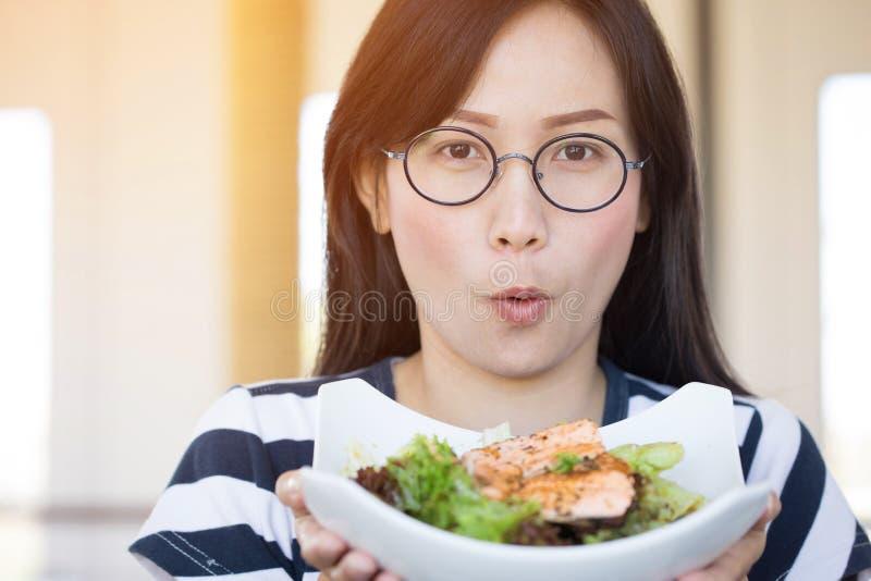 Donna asiatica di stile di vita sano che mostra sorridere dell'insalata immagini stock