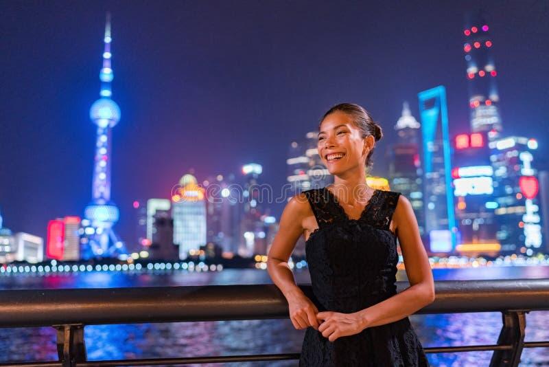 Donna asiatica elegante che sorride godendo del night-club che esce in vestito nero da modo dal fiume di Bund nella vista di Shan immagini stock libere da diritti
