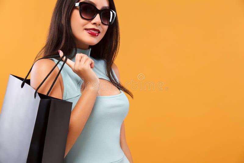 Donna asiatica felice ad acquisto che giudica borsa blu isolata su fondo arancio sulla festa nera di venerdì Copi lo spazio per immagine stock libera da diritti
