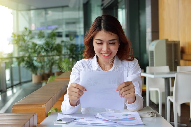 Donna asiatica felice attraente di affari che sorride con la carta del documento nel suo fondo dell'ufficio fotografia stock