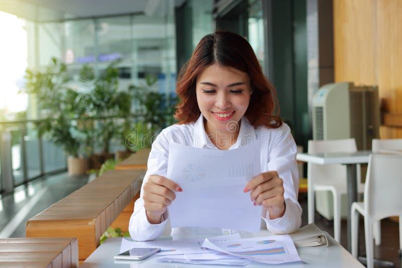 Donna asiatica felice attraente di affari che sorride con la carta del documento nel suo fondo dell'ufficio fotografie stock