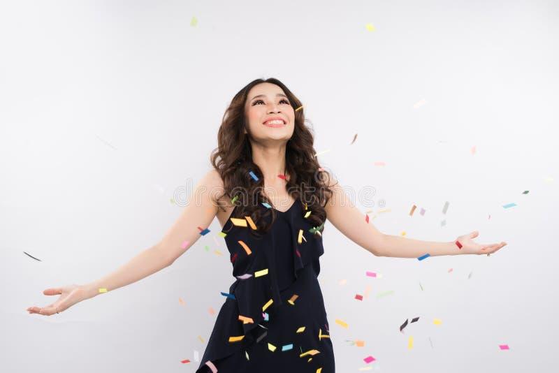 Donna asiatica felice che celebra con i coriandoli su fondo bianco fotografie stock libere da diritti