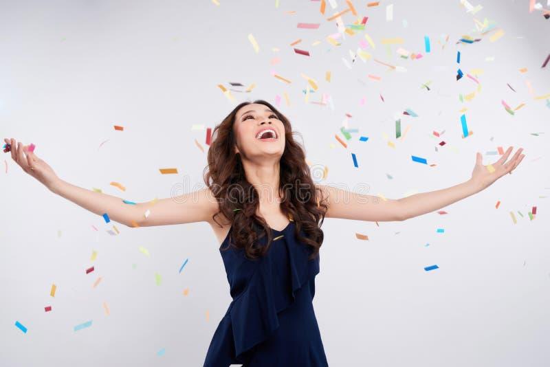 Donna asiatica felice che celebra con i coriandoli su fondo bianco fotografia stock