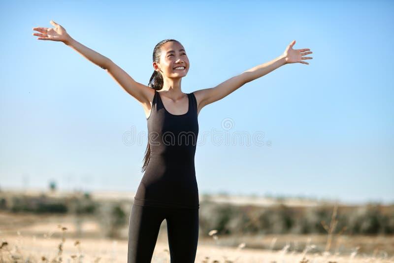 Donna asiatica felice che sta con a braccia aperte per incontrare sole fotografie stock libere da diritti