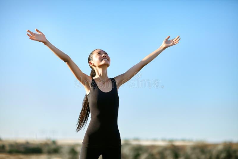 Donna asiatica felice che sta con a braccia aperte per incontrare sole fotografia stock libera da diritti