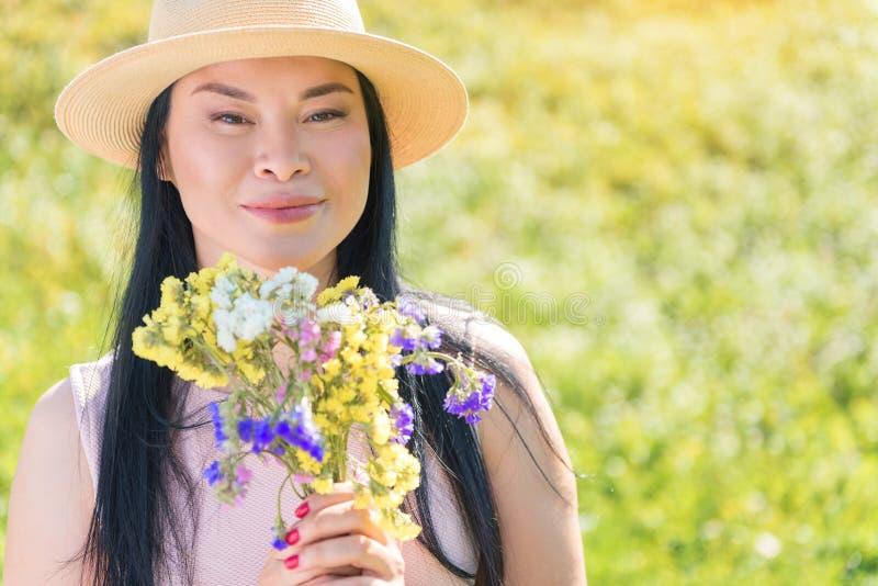 Donna asiatica felice con i fiori che si rilassano sul campo fotografia stock