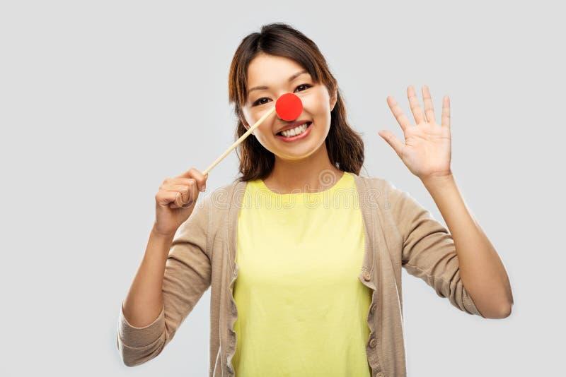 Donna asiatica felice con il naso rosso del pagliaccio immagine stock libera da diritti