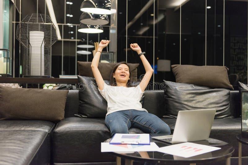 Donna asiatica felice di affari che utilizza un computer portatile nel salone a vicino immagine stock
