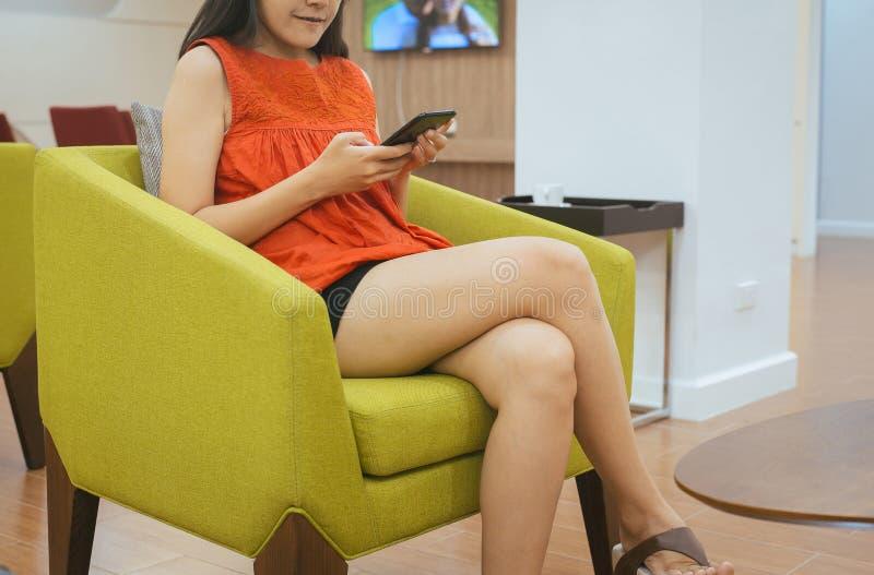 Donna asiatica felice e sorridente facendo uso di Internet di conection del telefono cellulare, chiacchierando, leggente messaggi immagine stock