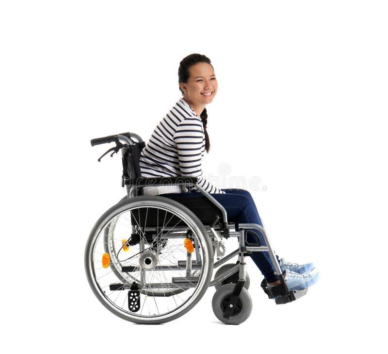 Donna asiatica felice in sedia a rotelle su fondo bianco fotografia stock