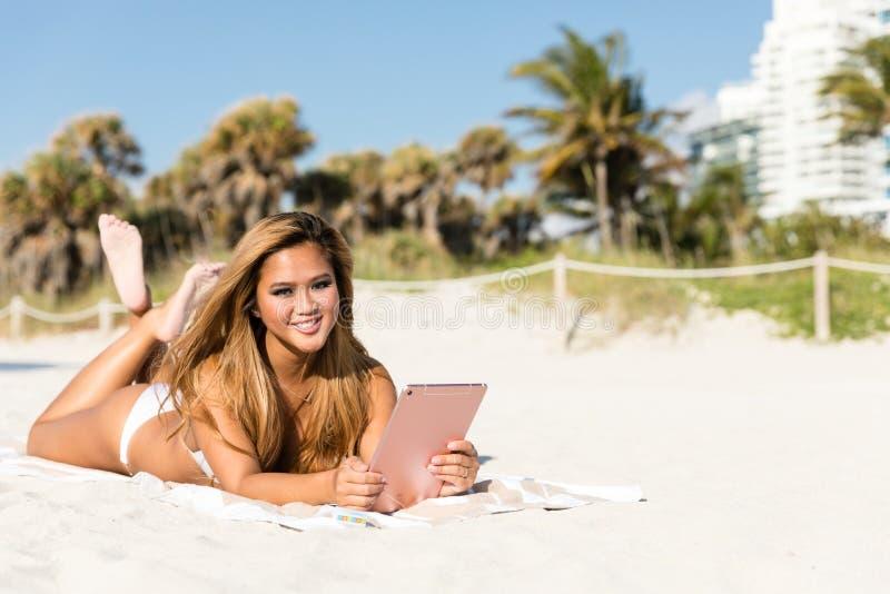 Donna asiatica felice sorridente che si trova sulla spiaggia facendo uso del computer della compressa immagine stock libera da diritti