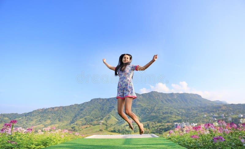 Donna asiatica giovane di salto che si sente libero con le armi spalancate ai bei alberi e montagne su cielo blu fotografia stock libera da diritti