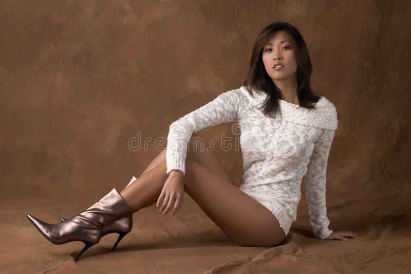 Donna asiatica in maglione ed in caricamenti del sistema fotografia stock libera da diritti