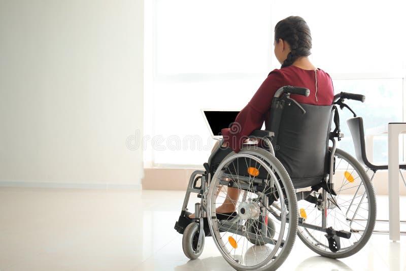 Donna asiatica nel funzionamento della sedia a rotelle con il computer portatile in ufficio fotografia stock libera da diritti