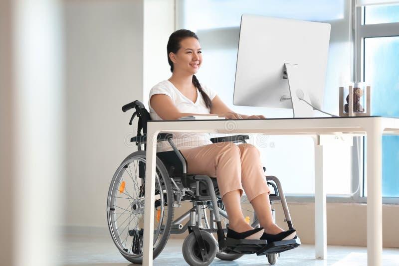 Donna asiatica nel funzionamento della sedia a rotelle con il computer in ufficio immagini stock