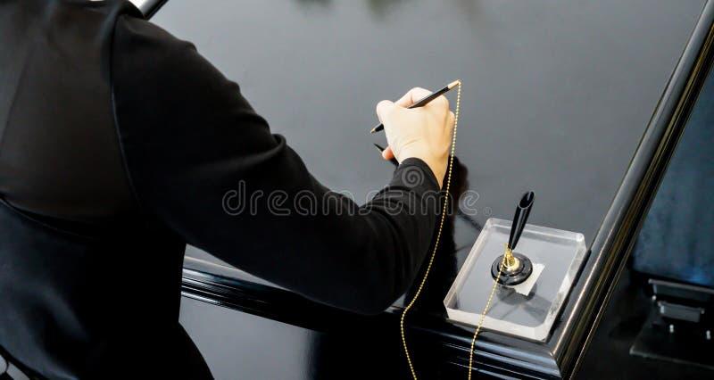 Donna asiatica nel nero che firma su con la sua mano destra fotografia stock