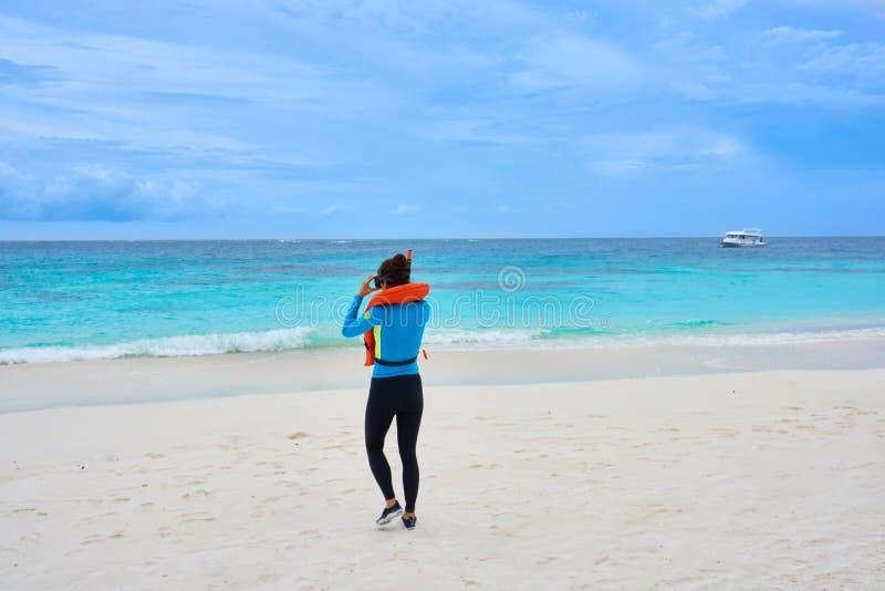 Donna asiatica nella guardia impetuosa alla spiaggia della località di soggiorno di Bodu Hithi dei Cochi che cammina verso il mar fotografia stock libera da diritti