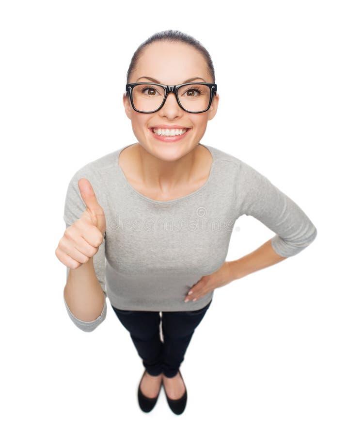 Donna asiatica in occhiali che mostrano i pollici su fotografia stock libera da diritti