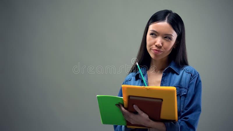 Donna asiatica occupata che annota i suoi piani ed idee, pianificazione quotidiana, lista di da fare fotografie stock libere da diritti