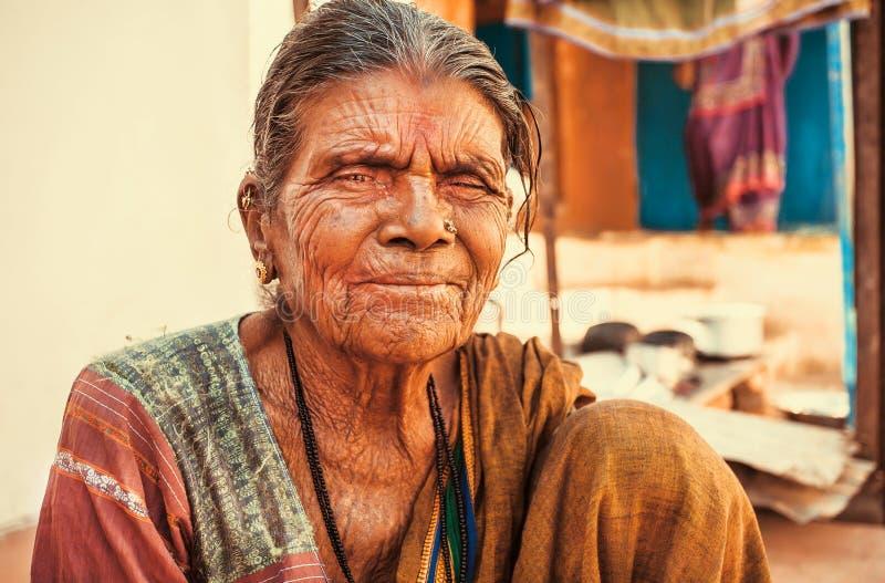 Donna asiatica più anziana con il fronte gentile e corrugato vivente nel villaggio indiano fotografie stock