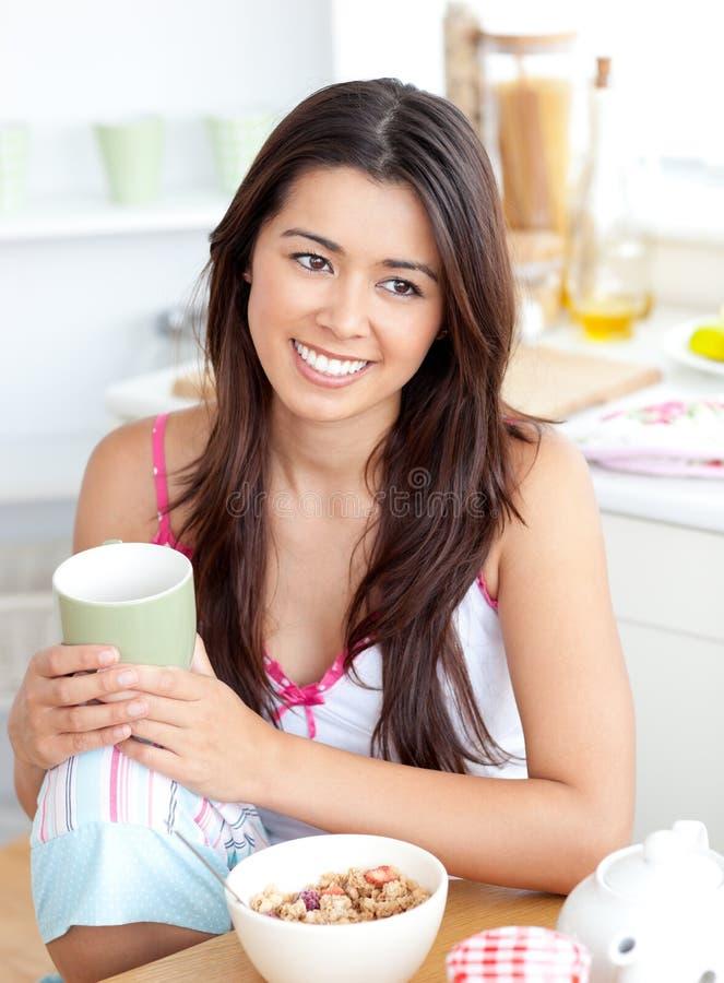 Donna asiatica radiante che tiene una tazza che si siede nel paese fotografia stock libera da diritti