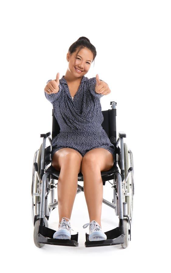 Donna asiatica in sedia a rotelle che mostra gesto di pollice-UPS su fondo bianco immagine stock