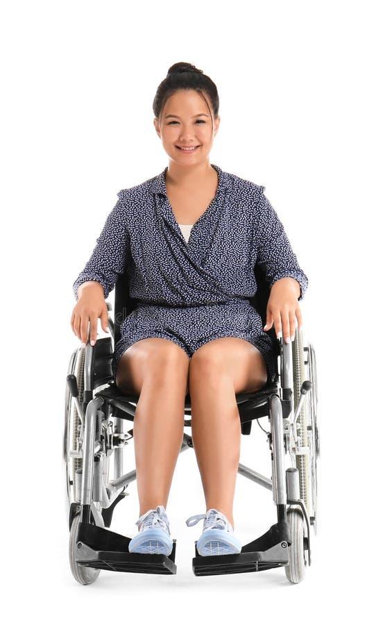 Donna asiatica in sedia a rotelle su fondo bianco immagini stock