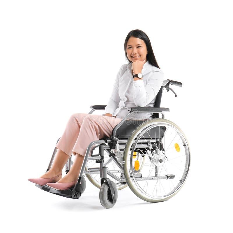 Donna asiatica in sedia a rotelle su fondo bianco immagine stock