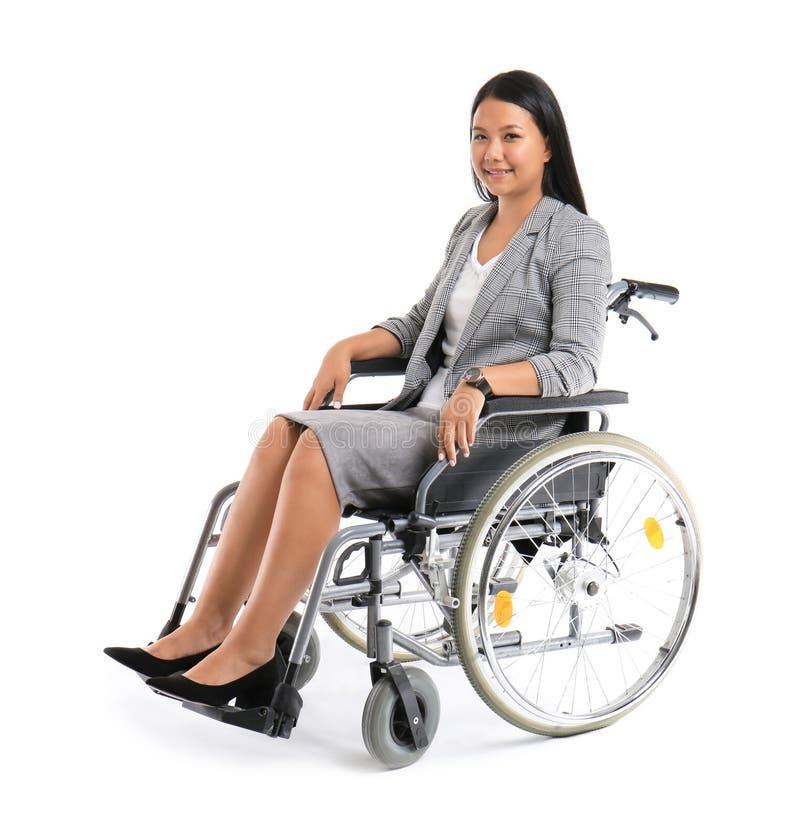 Donna asiatica in sedia a rotelle su fondo bianco immagini stock libere da diritti