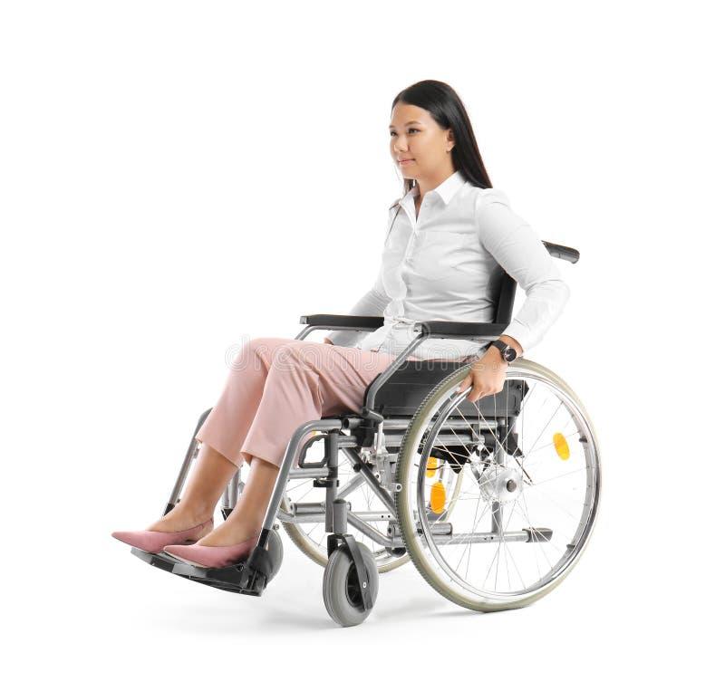 Donna asiatica in sedia a rotelle su fondo bianco fotografie stock