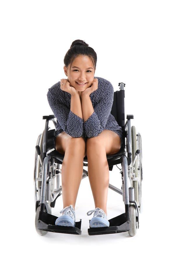 Donna asiatica in sedia a rotelle su fondo bianco fotografia stock libera da diritti