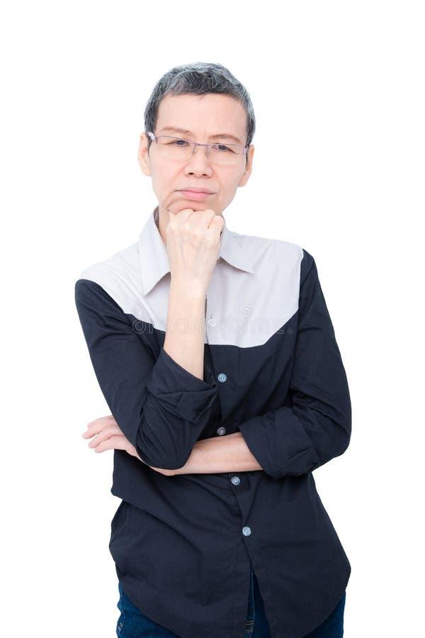 Donna asiatica senior che pensa sopra il bianco fotografia stock