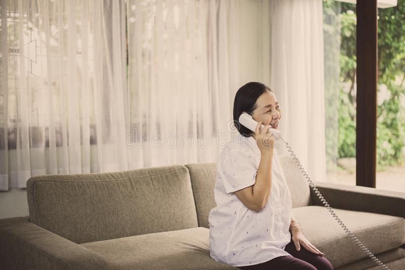 Donna asiatica senior felice che parla sul telefono a casa fotografie stock