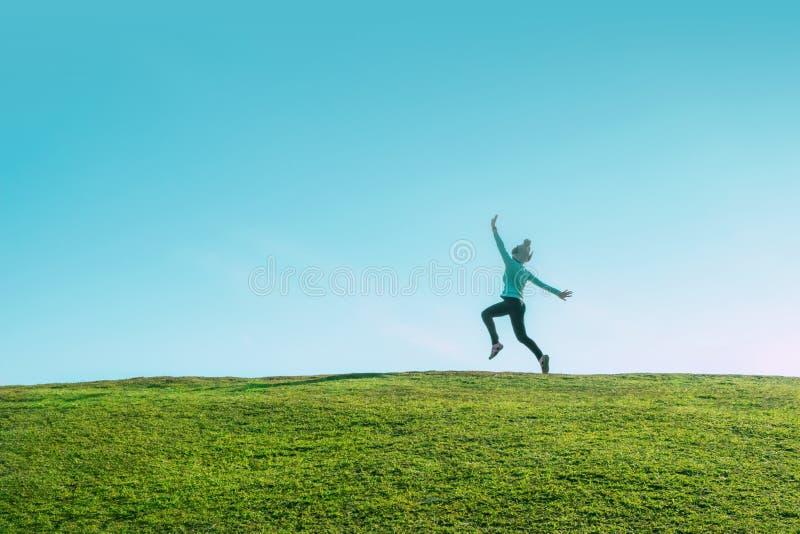 Donna asiatica sola che salta per la gioia su una collina dell'erba sopra la linea una mosca esile felice di orizzonte della raga fotografie stock