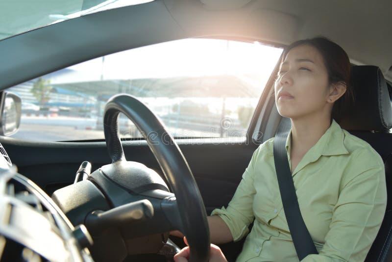 Donna asiatica sonnolenta stanca di affari che conduce un'automobile fotografia stock libera da diritti