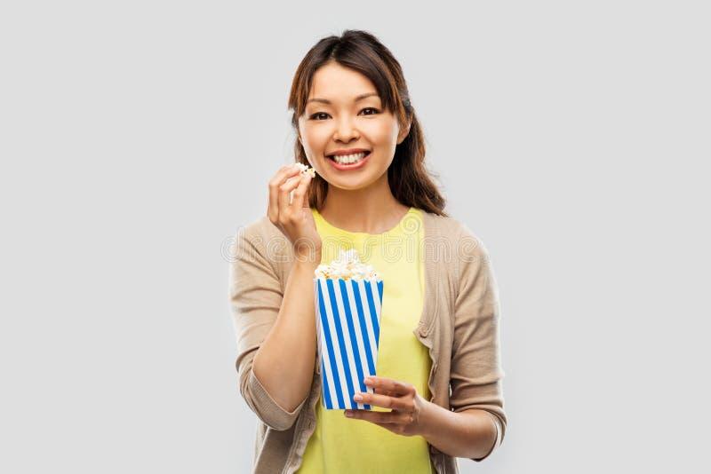 Donna asiatica sorridente che mangia popcorn fotografie stock libere da diritti