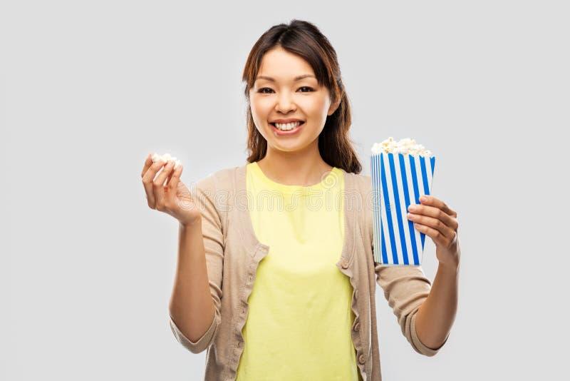 Donna asiatica sorridente che mangia popcorn fotografie stock