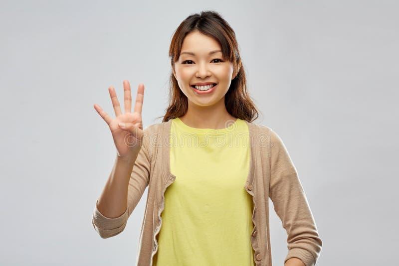 Donna asiatica sorridente che mostra quattro dita immagine stock libera da diritti