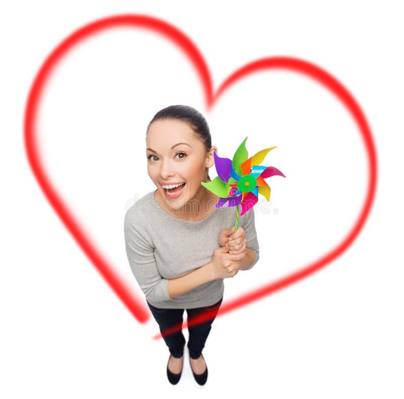 Donna asiatica sorridente con il mulino a vento fotografie stock libere da diritti