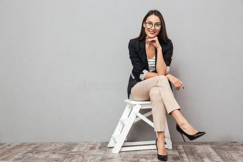 Donna asiatica sorridente di affari in occhiali che si siedono sulla sedia fotografie stock