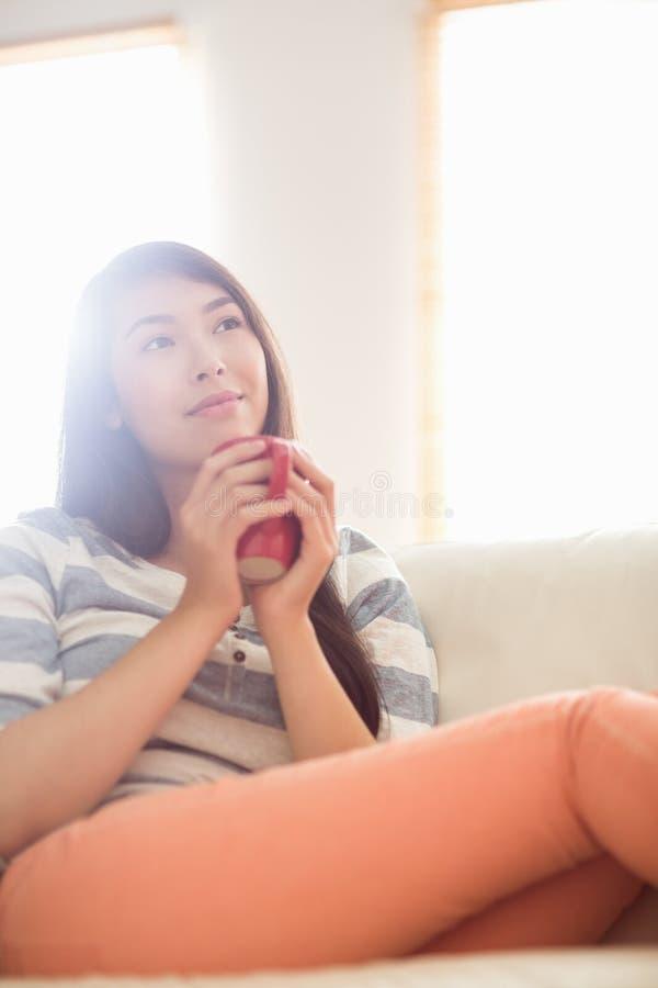 Donna asiatica sorridente sullo strato che ha bevanda calda fotografia stock libera da diritti