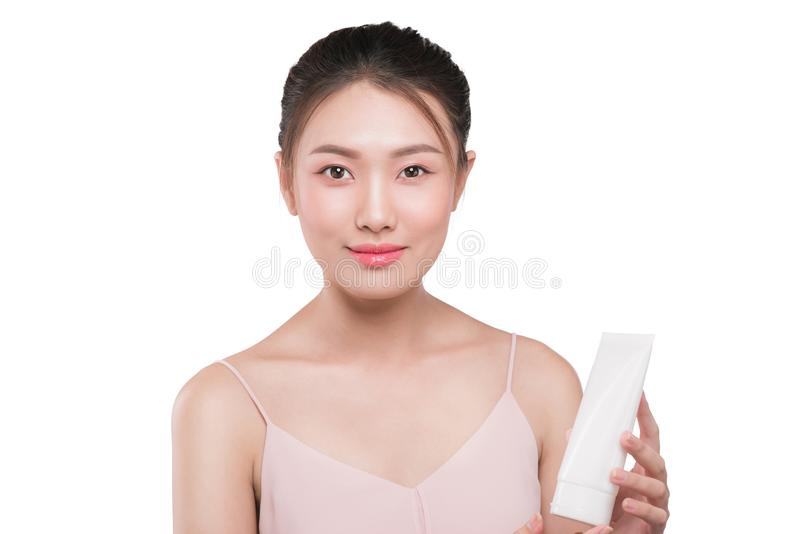 Donna asiatica splendida che sorride e che tiene la crema di fronte Colpo dello studio fotografia stock libera da diritti