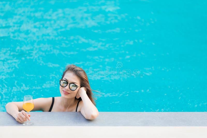 Donna asiatica in stagno con vetro di succo d'arancia fotografia stock libera da diritti