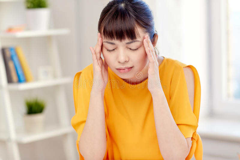 Donna asiatica stanca che soffre dall'emicrania a casa immagini stock libere da diritti