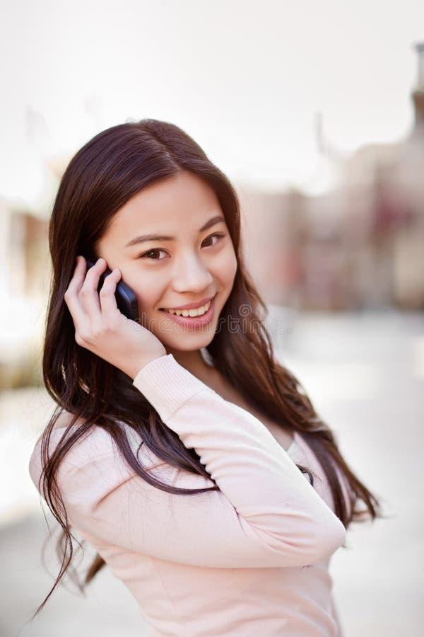 Donna asiatica sul telefono fotografie stock
