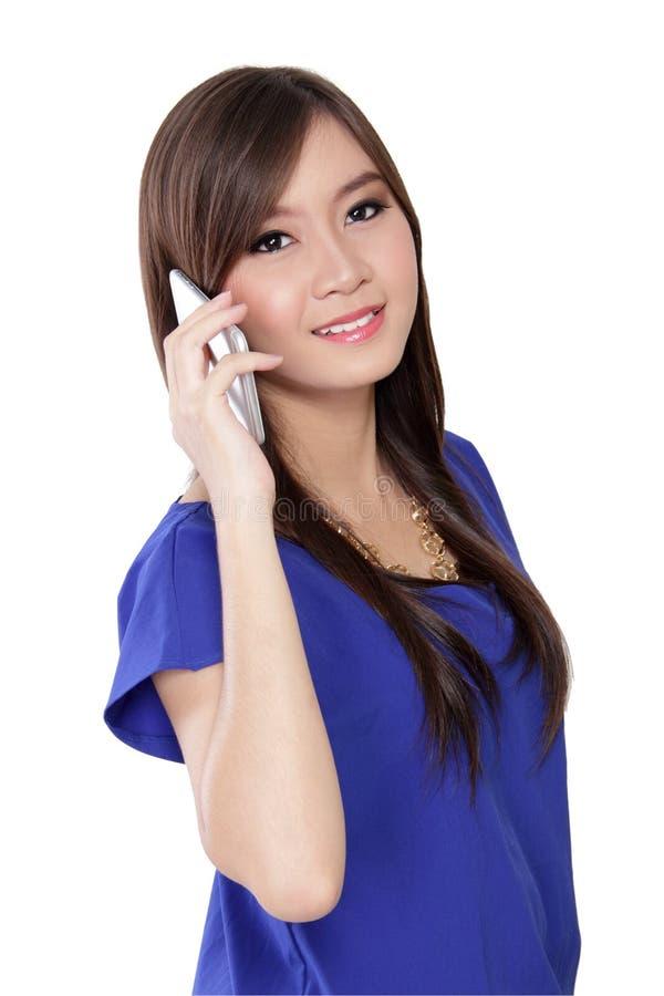 Donna asiatica sul telefono che sorride alla macchina fotografica immagine stock libera da diritti