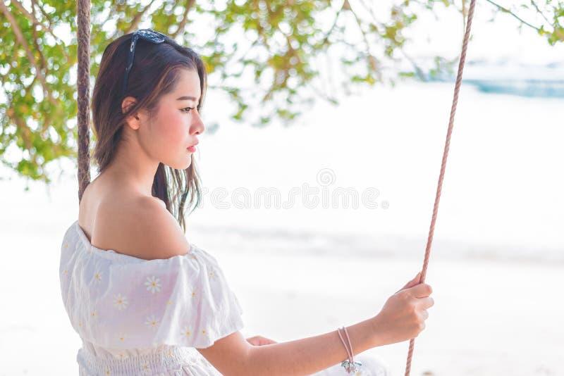 Donna asiatica sul vestito bianco che si siede sull'oscillazione alla spiaggia La gente e fotografia stock libera da diritti