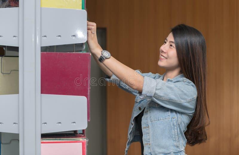 Donna asiatica sveglia che seleziona libro a partire da uno scaffale per libri fotografia stock libera da diritti