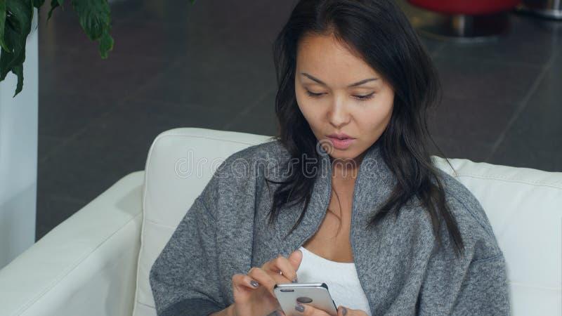 Donna asiatica sveglia che si rilassa sul sofà e che per mezzo dello smartphone fotografie stock libere da diritti